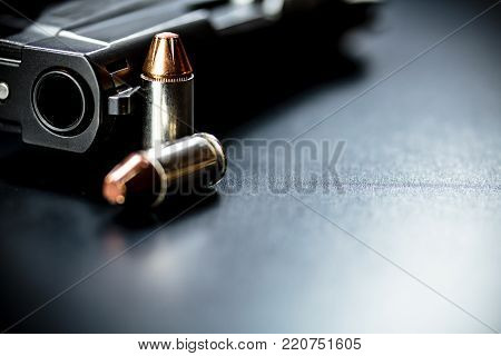 A hand gun pistol bullets on a plain background.