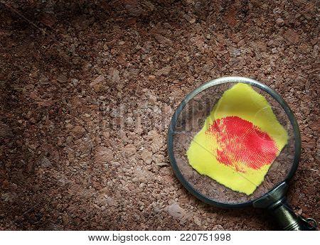 Crime investigation concept. Old magnifying glass above red finger print