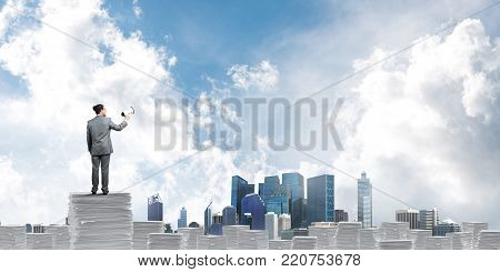 Businessman in suit standing on pile of documents with speaker in hand with skyscape and city view on background. Mixed media. poster