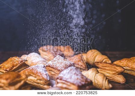 Sugar powder is poured onto buns from puff pastry. Freshly baked pastry rolls and croissants close-up. Croissants and puff pastries lie on the table. Buns lie on a wooden table.
