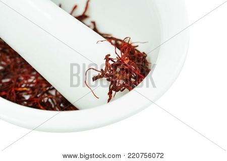 Dried saffron threads in white ceramic mortar isolated on white (Crocus sativus)