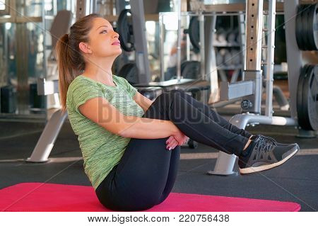 Sporty young attractive woman practicing abdominal, crunches, sit ups, rock press exercise, working out. Healthy lifestyle, gymnastics, weightloss concept