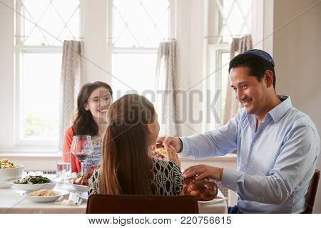 Jewish man sharing challah bread with family at Shabbat meal