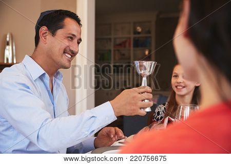 Jewish man holding kiddish cup blesses family at Shabbat
