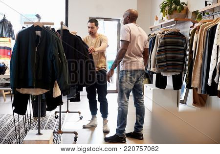 Shop assistant helping customer in a menÃ?s clothes shop