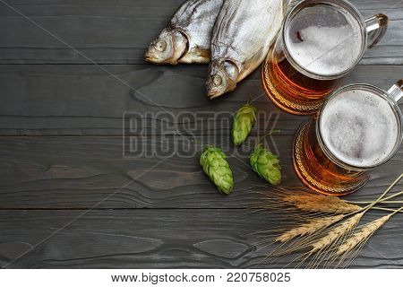 Glass beer with hop cones, dried fish and wheat ears on dark wooden background. Beer brewery concept. Beer background. top view with copy space