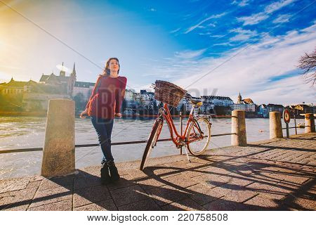 A beautiful young girl stands on the embankment near a city bike with a red basket in Switzerland, the city of Basel is far away cathedral and old houses. Sunny day in old Europe