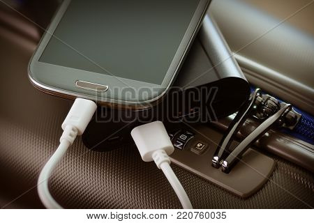 Smart cellular mobile phone charging with power bank on the travel bag or luggage. Macro shot
