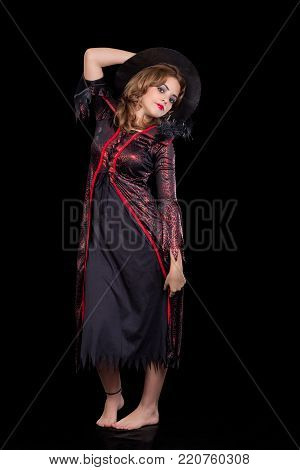 girl dressed as a witch portrayed on black background, wearing black pointing hat