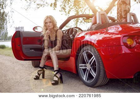 sexy girl on a cabrio. traveling by car with a beautiful girl hitchhiking