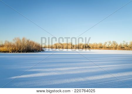 frozen lake with along sunset shadows, Fort Collins in northern Colorado