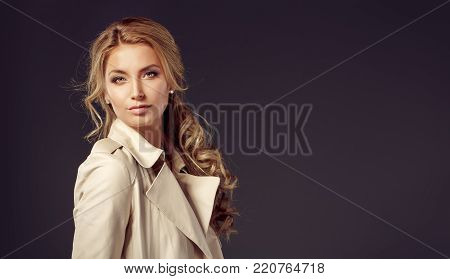 Portrait of young blonde haired woman in beige overcoat looking at camera seductively against of black background