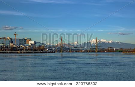 Residential District in New Westminster City with new construction at the waterfront of   Fraser River and three bridges at the bakground of blue ske and snow caped mountain range