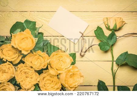 Message card tied to a yellow rose - Greeting card idea with roses bouquet and a separate rose with a blank message card attached to it with a linen string, on a yellow wooden table.