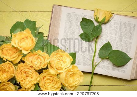 Yellow rose on an open old book - Beautiful single yellow rose on an open vintage book, displayed on a yellow wooden table and a bouquet of roses, blurred, in the foreground.