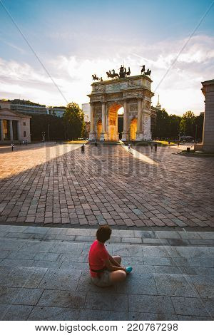 girl tourist looking atArch of Peace in Sempione Park, Milan, Lombardy, Italy. Arco della Pace aka Porta Sempione in Milan, Italy.