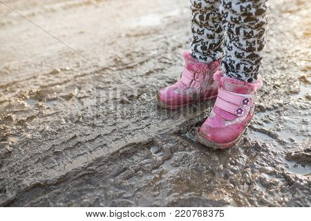 Concept is a happy childhood, child in swamp, children's fun, dirty shoes, life in the village, sunlight, Ukraine. Place for text