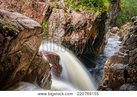 Small waterfall between red and orange rocks on river in Glen Nevis, Scotland, United Kingdom. Scottish nature and travel theme.