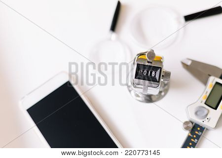 Concept Of Happy New Year 2018 Celebration. Number Hand Tally Counter With Engineering Tool On White