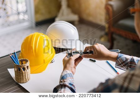 Architect or Construction Engineer working a construction project on drawing table with engineering tool in office. Construction engineering.Selective focus.