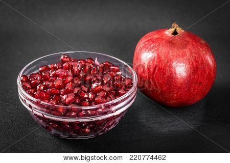 The seeds from a pomegranate fruit in a bowel.  A whole pomegranate is beside the bowel