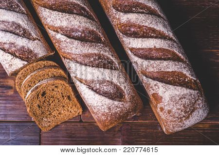 A view of a loaf of rye bread on a wooden table. Loaves of rye bread lie next to each other. Sliced pieces of bread lie near the loaf. Bread is strewn with white flour.