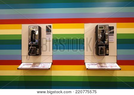 SINGAPORE- 10 DEC, 2017: Two pay phone on the colorful wall in Changi Airport, Singapore.