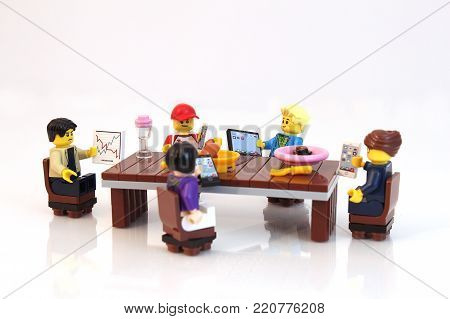 Colorado, USA - January 5, 2018: Studio shot of Lego minifigure people at dinner table all on their phone and devices ignoring each other.