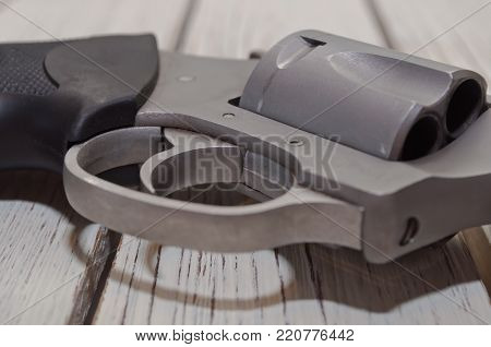 A close up of the trigger, cylinder and butt of a stainless revolver on a white wooden table