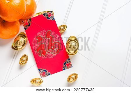Top view Chinese New year red envelope packet ( ang pow ) with gold ingots and tangerine on white wood table top,Chinese Language on envelop mean Happiness and on ingot mean Wealthy poster