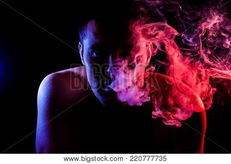 Man  is admiting puffs of steam from the electronic cigarette, cloud of colored smoke of blue, green, orange  color on a black isolated.  Harm to smoking on the example of a young mugger