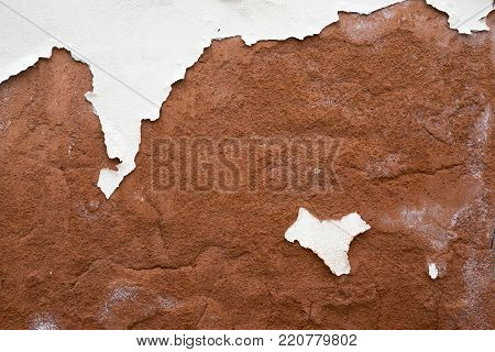 red plaster wall background with peeled off white paint