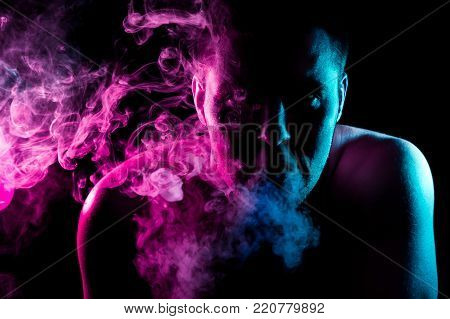 A young man exhales a cloud of colored smoke of red and green color on a black isolated color.  Guy is admiting puffs of steam from the electronic cigarette.