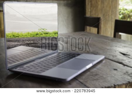 Modern grey metal laptop on wooden table, stock photo