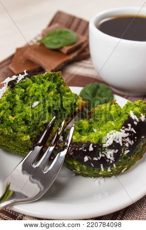 Homemade muffins baked with wholemeal flour with spinach, desiccated coconut and chocolate glaze, cup of coffee