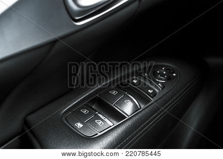 Car black perforated leather interior details of door handle with windows controls and adjustments. Car door handle inside the luxury modern car. Switch button control