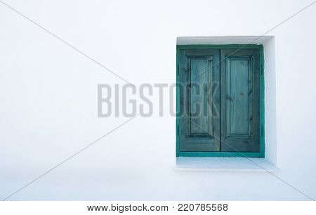Green wooden closed window on a white wall.