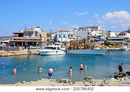 SISSI, CRETE - SEPTEMBER 14, 2016 - Tourists in the sea along the rocky shoreline with views of boats and restaurants to the rear, Sissi, Crete, Greece, Europe, September 14, 2016.