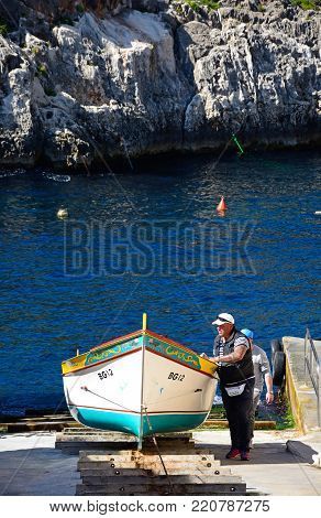 BLUE GROTTO, MALTA - APRIL 1, 2017 - Men pulling a traditional Dghajsa water taxi up a ramp for mooring at the departure point, Blue Grotto, Malta, Europe, April 1, 2017.