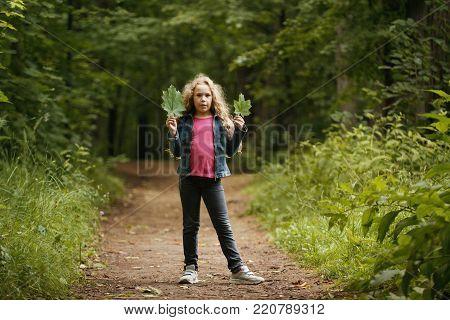 Little girl with curly hair holds leaves in hands - outdoor portrait, telephoto shot