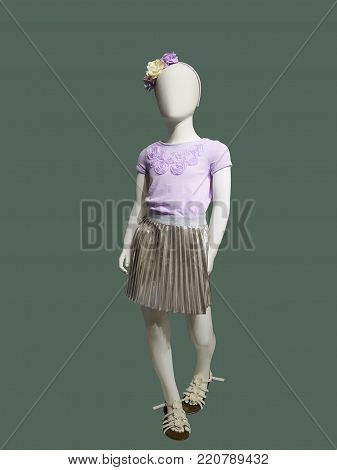Full-length child mannequin dressed in fashionable clothes, isolated on green background. No brand names or copyright objects.