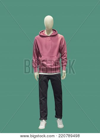 Full-length male mannequin dressed in casual clothes (sweatshirt and trousers), isolated on green background.  No brand names or copyright objects.