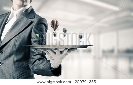Closeup of waiter's hand in glove presenting flying aerostats on metal tray with office view on background. 3D rendering.