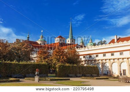 PRAGUE - June 16th:  The view on the towers and rooftops of St Josef and St Nicholas church from the Wallenstein Garden on June 16th, 2017 in Prague, Czech Republic. Red rooftops of Lesser Quarter ancient buildings on the background of blue sky.