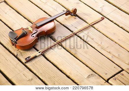 Violin and string on wooden pier. Love of music concept
