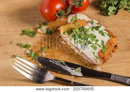 Pork schnitzel with white sauce and parsley on wooden cutting board