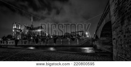 Notre Dame de Paris cathedral at night black and white. Ile de La Cite  (Place Jean-Paul II) 4th Arrondissement Paris France