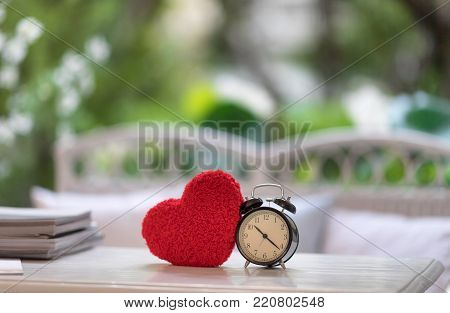 clock with red heart knitting shape on wooden mock up over blurred green garden on day noon light,Image for happy valentine day decoration concept. over blurred green garden .happy valentine day decoration concept.
