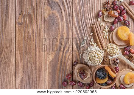 Mix of nuts, dried fruits, dried rose hips, and spices on a rustic wooden background. Concept of healthy snack. Various nuts and dried fruits.