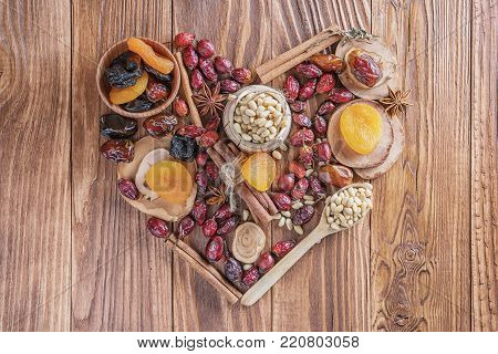 Mix of nuts, dried fruits, dried rose hips, and spices in the shape of a heart on a rustic wooden background. Concept of healthy snack. Various nuts and dried fruits with copy space.